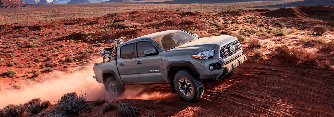 2018 Toyota Tacoma driving uphill on a dirt road